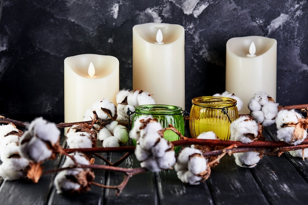Cotton flowers lying on a dark wooden background and candles