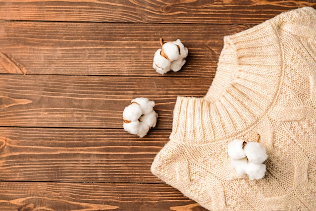 Cotton flowers with knitted sweater on wooden background
