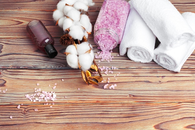 Cotton flowers with towel on wooden table