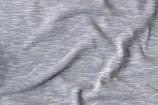 コットンジャージー生地の風合い。しわくちゃの灰色のテキスタイルの背景