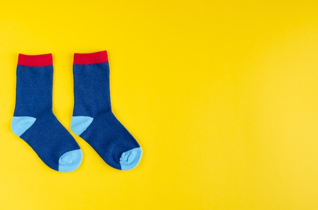 Cotton kids socks composition on yellow background.