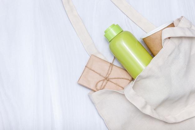 면화 린넨 백, 스테인리스 스틸 병, 무료 플라스틱 쇼핑을위한 종이컵. 친환경 개념. 공간을 복사하고 평평하게 놓습니다.