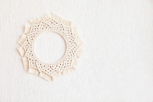 白い壁に掛かっている綿のマクラメ曼荼羅の壁の装飾。手作りのマクラメの花輪。天然綿糸。エコ家の装飾。