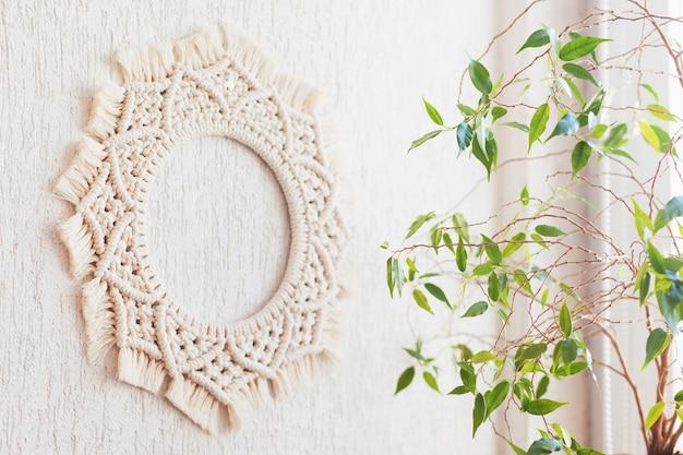 緑の葉と白い壁に掛かっている綿のマクラメ曼荼羅の壁の装飾。手作りのマクラメの花輪。天然綿糸。エコ家の装飾。