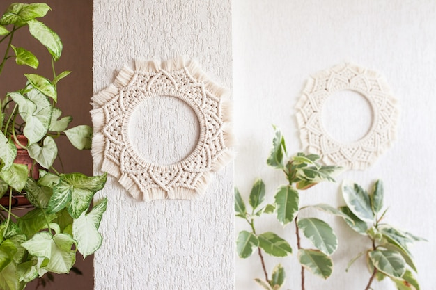 Cotton macrame mandala wall decoration hanging on white wall with green leaves. handmade macrame wreath. natural cotton thread. eco home decor.