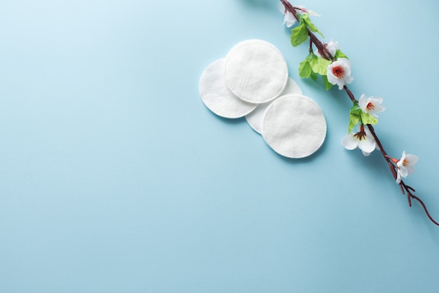 Cotton pads for removal makeup with white flowers on the blue background flatlay