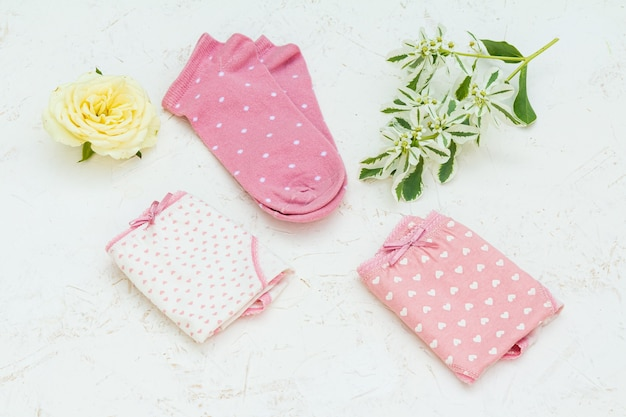 Cotton panties with flowers and pink women socks on the white structured background. top view.