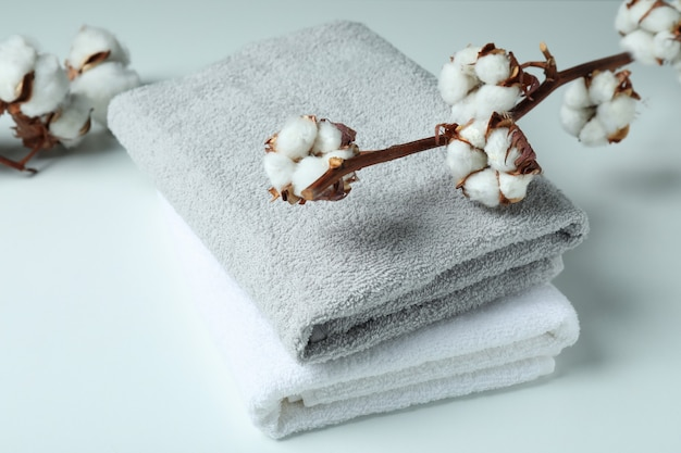 Cotton plant branches and towels on white