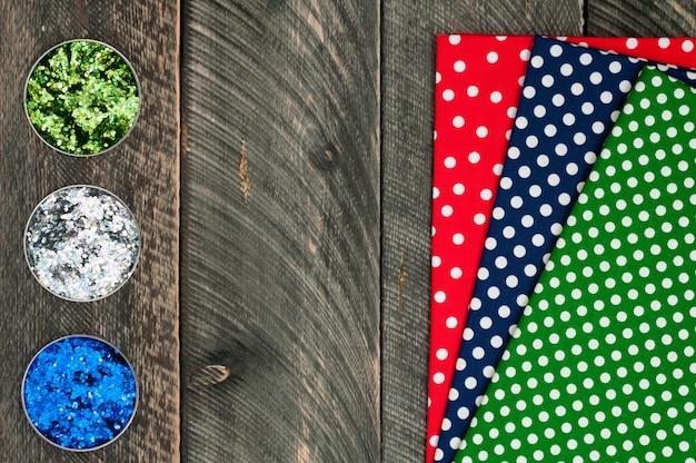 Хлопковый текстиль в горошек для рукоделия и блеск на старом деревянном фоне
