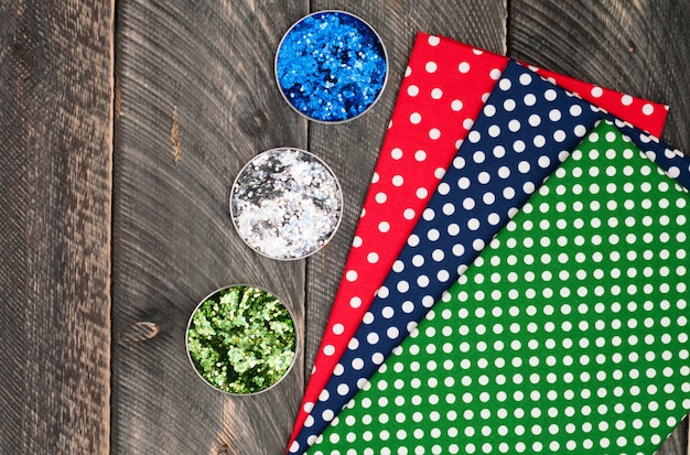Cotton polka dots textile for needlework and glitter on old wooden background. top view