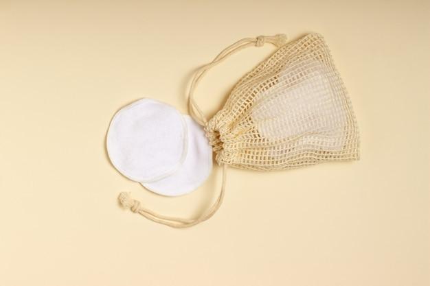 Многоразовые хлопковые подушечки для снятия макияжа в тканевом мешочке на бежевом фоне. понятие экологии и осознанного потребления. многоразовые ватные диски