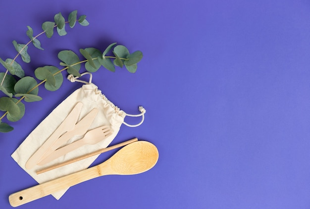 Cotton small bag and eucalyptus leaves on blue surface