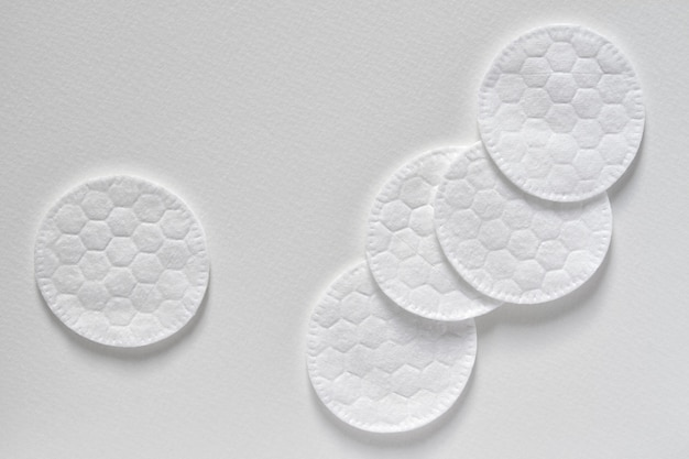 Cotton sponges or cotton cosmetic pads on the light background. closeup, top view