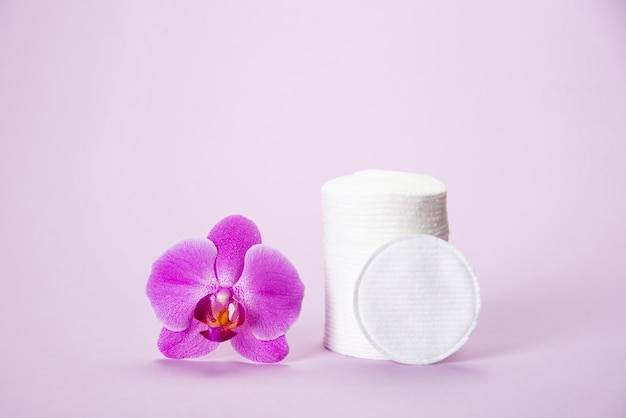 Cotton sponges in a glass jar on a pink background with an orchid flower
