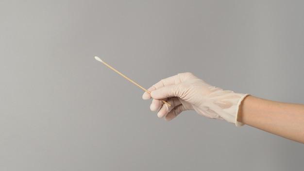 Ватная палочка для мазка в руке с белыми медицинскими перчатками на сером фоне.