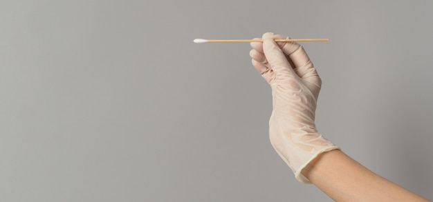 Cotton stick for swab test in hand with white medical gloves on grey background.