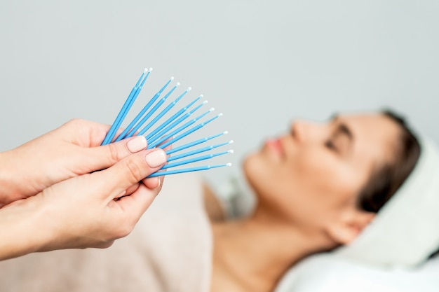 Cotton sticks for eyelashes in hands on background of woman.