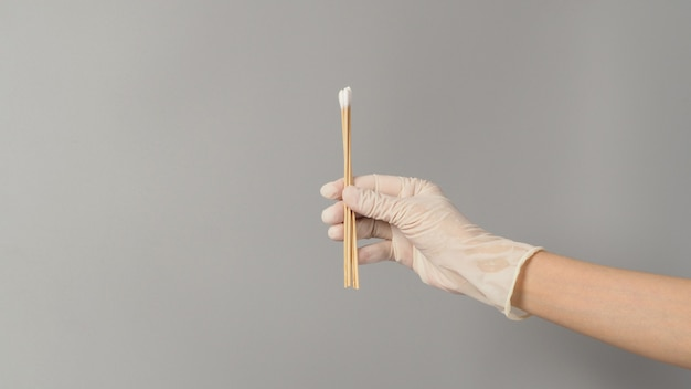 Cotton sticks for swab test in hand with white medical gloves on grey background.