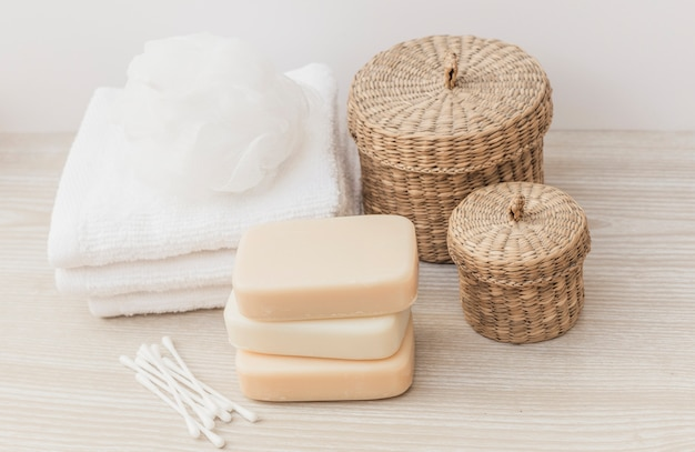 Cotton swab; soaps; towel; loofah and wicker basket on wooden tabletop