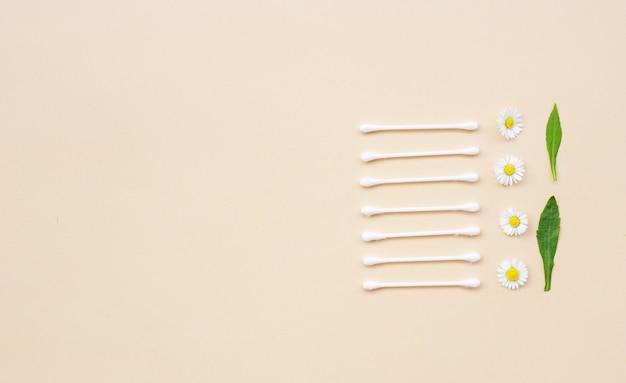 베이지색 배경에 면봉과 신선한 카모마일. 평평한 평지, 평면도, 복사 공간. 여성 건강 관리