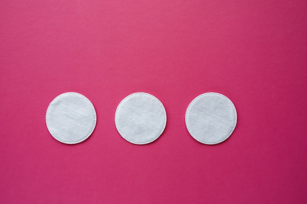 Cotton swabs and disks isolated on a pink background. hygiene products.