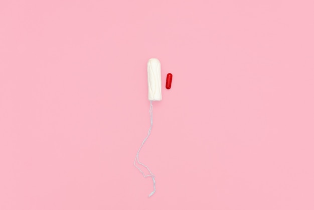 Cotton tampon on pink background.