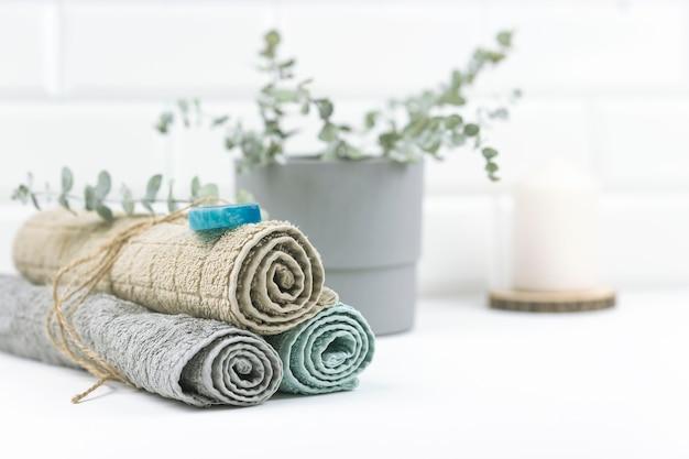手作り石鹸を塗ったニュートラルカラーのコットンタオルがモダンなバスルームのテーブルに置かれています