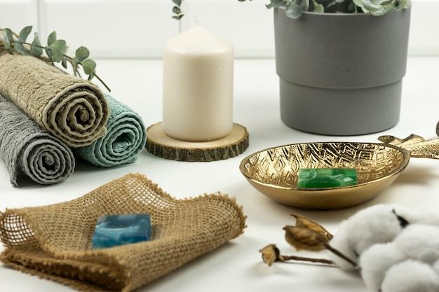 ユーカリの枝が付いたニュートラルカラーのコットンタオルがモダンなバスルームのテーブルに置かれています