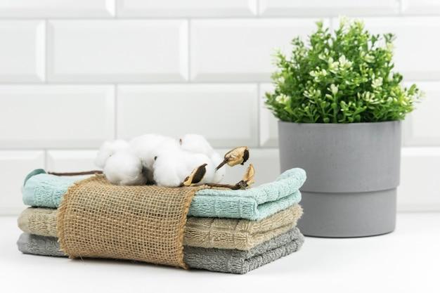 モダンなバスルームのテーブルの上に、綿の枝が付いたニュートラルカラーのコットンタオルが置かれています。
