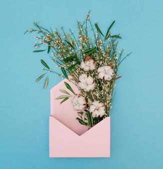 Хлопок с травами в розовом конверте на синем фоне. вид сверху