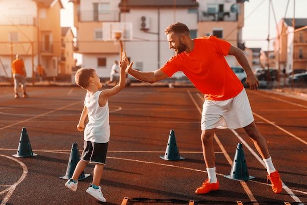 Диван дает высокий спортивный мальчик, стоя на площадке утром в летнее время.