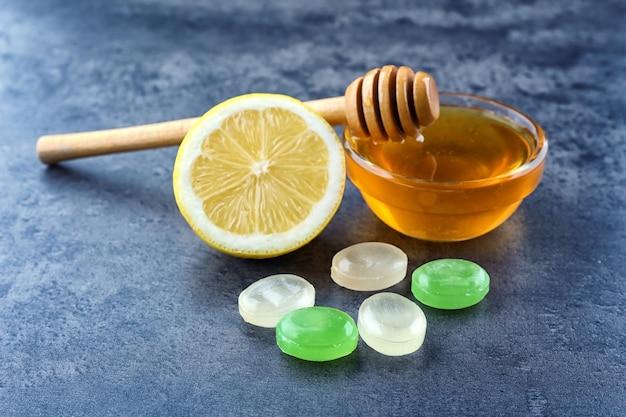色の背景に蜂蜜とレモンと咳止めドロップ