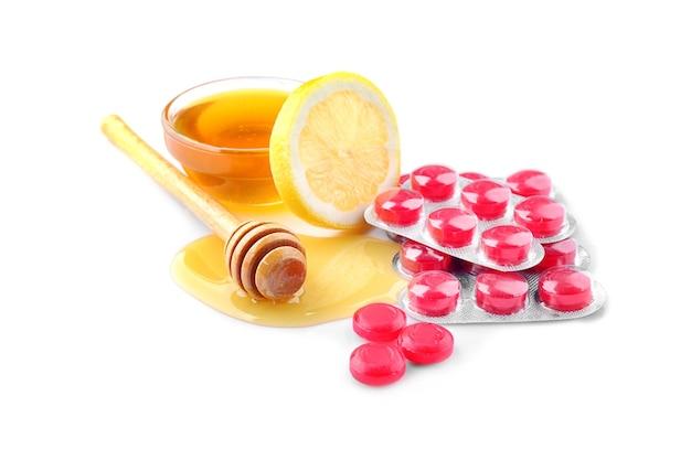 白い背景の上の蜂蜜とレモンと咳止めドロップ
