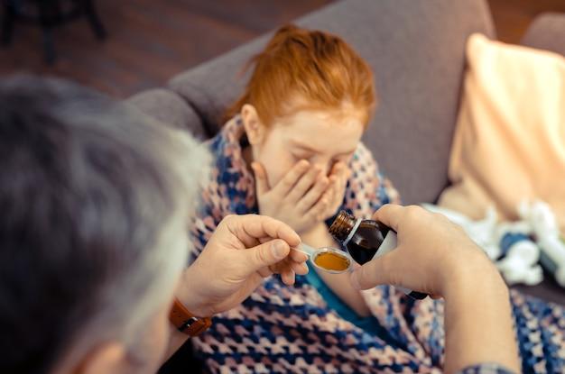 Лекарства от кашля. селективный фокус ложки со смесью от кашля, находящейся в мужских руках