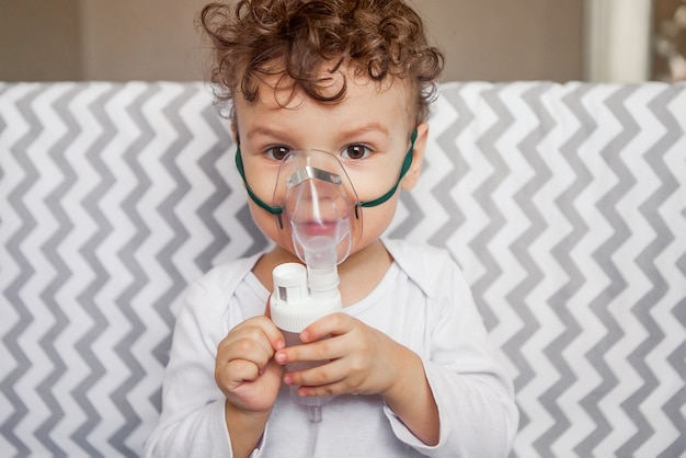 Cough treatment by inhalation. baby with a nebulizer in his hands, breathing mask on his face