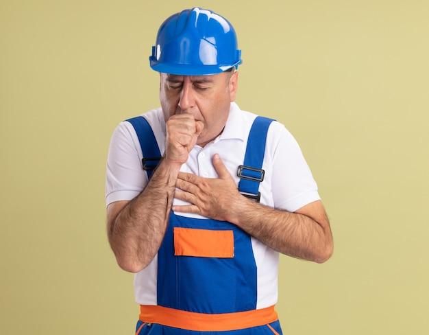 Tosse uomo costruttore adulto in uniforme mette la mano sul petto e tiene il pugno vicino alla bocca isolato sulla parete verde oliva