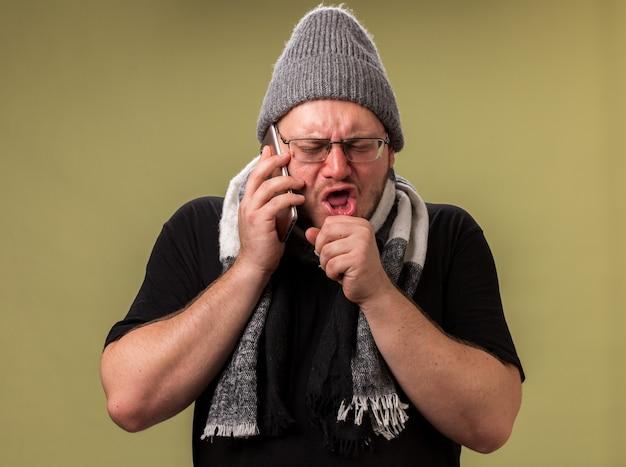 Tosse maschio malato di mezza età che indossa cappello invernale e sciarpa parla al telefono isolato su muro verde oliva