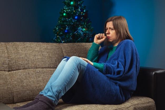 장식된 크리스마스 트리가 있는 소파에서 기침하는 여자 아플 때 축하하는 방법