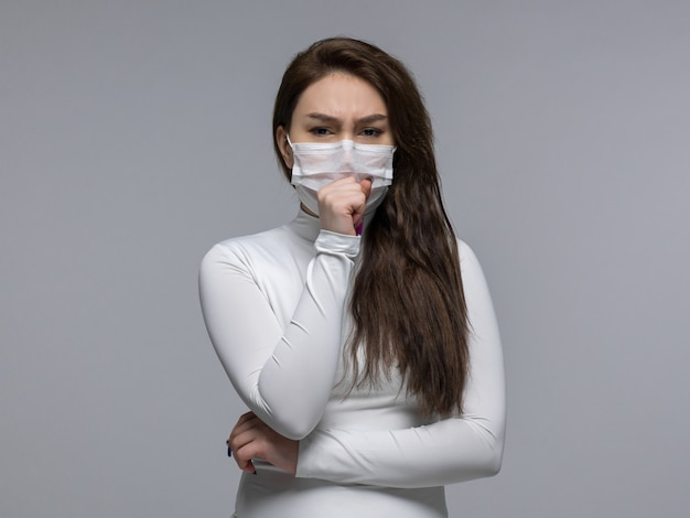 Coughing woman with painful expression in white protective mask