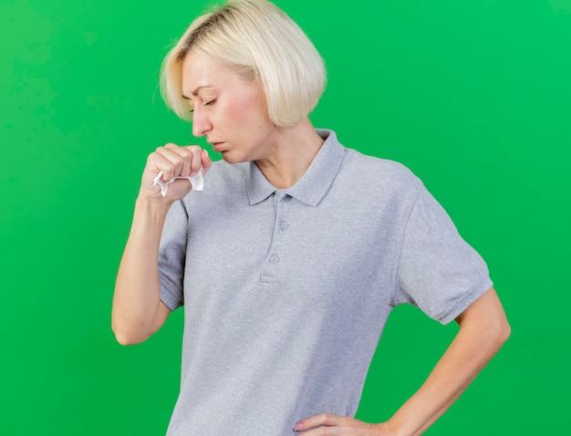 기침 젊은 금발 아픈 슬라브 여자는 녹색에 고립 된 조직을 보유