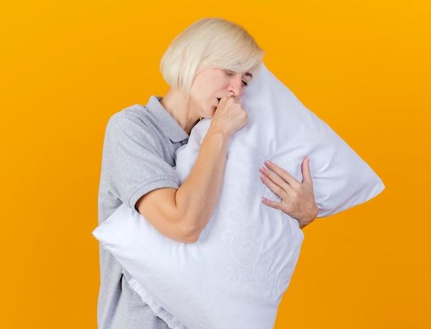La giovane donna bionda malata di tosse abbraccia il cuscino isolato sulla parete arancione