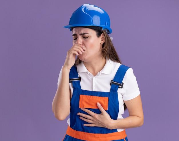 Tossendo le giovani donne del costruttore in uniforme che mettono la mano sulla bocca isolata sulla parete viola