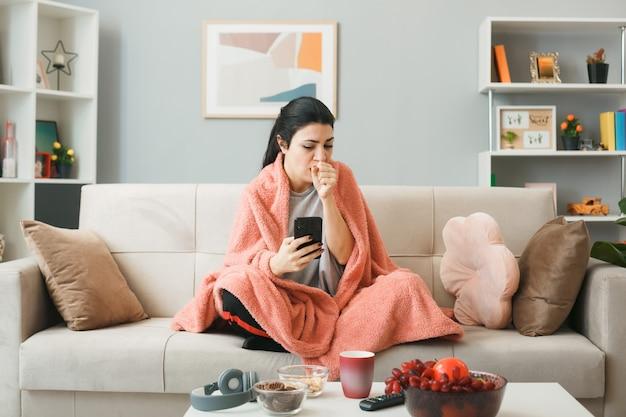 거실에서 커피 테이블 뒤에 소파에 앉아 전화를 들고 격자 무늬에 싸여 기침 어린 소녀