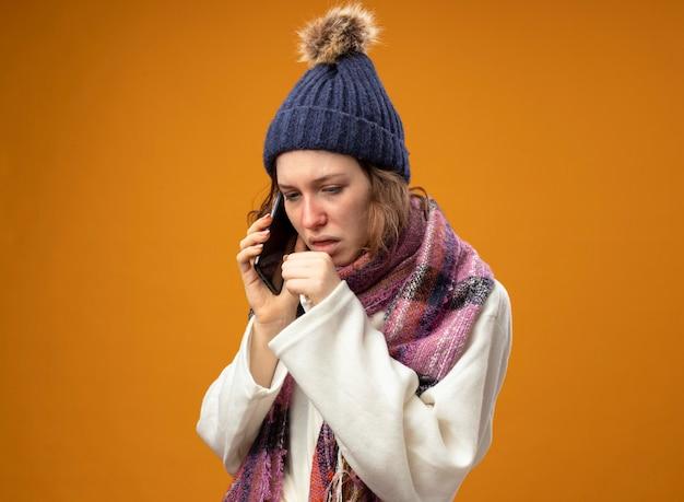 白いローブとスカーフと冬の帽子を身に着けて見下ろしている咳の若い病気の女の子は、オレンジ色に分離された口に手を置いて電話で話します