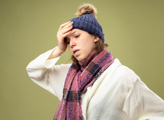 Tosse giovane ragazza malata guardando al lato che indossa una veste bianca e cappello invernale con sciarpa che mette la mano sulla fronte isolata su verde oliva