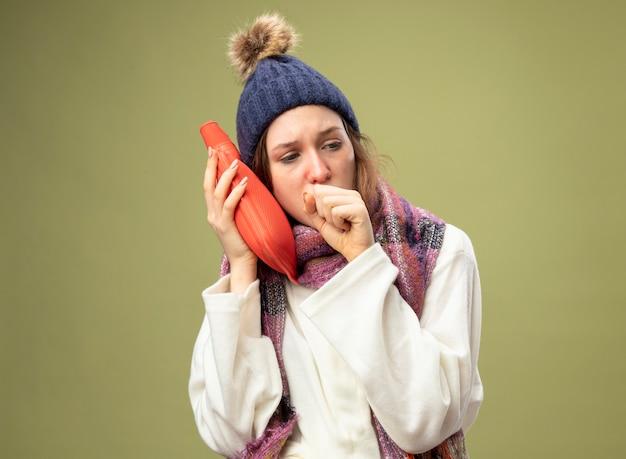 Tosse giovane ragazza malata guardando al lato che indossa una tunica bianca e cappello invernale con sciarpa mettendo il sacchetto di acqua calda sulla guancia isolato su verde oliva