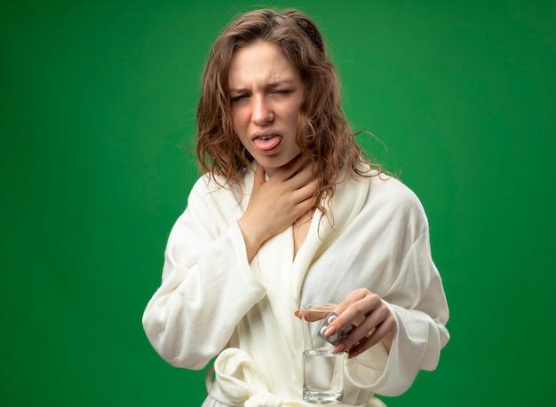 緑に分離された水のガラスをつかんだ喉を保持している白いローブを着て咳をする若い病気の女の子