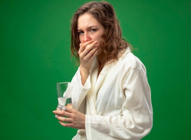 Tosse giovane ragazza malata che indossa una veste bianca tenendo il bicchiere d'acqua e mettendo la mano sulla bocca isolato su verde