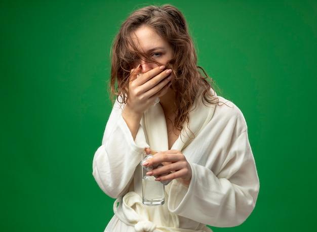 Tosse giovane ragazza malata che indossa una veste bianca tenendo il bicchiere d'acqua con le pillole e la bocca coperta con la mano isolata sul verde