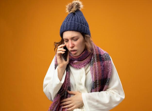 Tosse giovane ragazza malata che indossa una veste bianca e cappello invernale con sciarpa parla al telefono mettendo la mano sullo stomaco isolato sulla parete arancione
